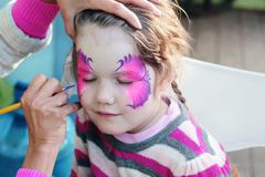 Female hand drawing purple butterfly on face of beautiful little girl - stock photo