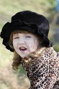Beautiful little girl in black hat shouts outdoor at autumn day. - stock photo