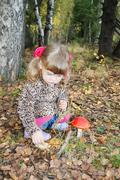 Pretty little girl with pink bows in overcoat sits next red toadstool in fore - stock photo