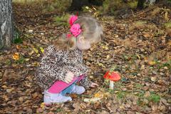 Pretty little girl with pink bows in overcoat looks at red toadstool in fores Stock Photos