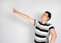 Brunet man in striped T-shirt smiles and points to side on grey background. - stock photo