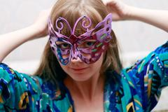 Beautiful smiling woman in colored dress poses in violet shiny mask - stock photo
