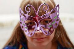 Beautiful smiling woman in colored dress looks at camera in violet shiny mask - stock photo