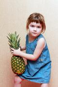 Little beautiful girl in jeans dress holds big green pineapple indoor Stock Photos
