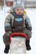 Little boy wearing warm jumpsuit sits on seesaw at winter day - stock photo