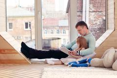 Pretty little blonde girl and father sit near window and read book at home Stock Photos