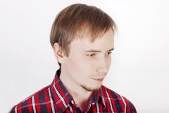 Young man with beard in checkered red shirt thinks and looks away - stock photo