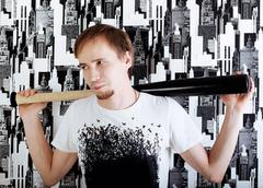 Young man with beard in white shirt stands with bat near wall Stock Photos
