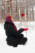 Smiling girl sits on snow and looks at hanging in air big red apple outdoor a Stock Photos