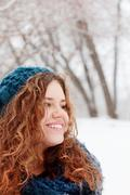 Pretty girl in blue beret smiles and looks away at winter day in park - stock photo