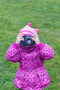 Little girl in pink photographs by camera rarity outdoors at autumn day - stock photo