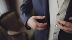 Groom buttoning his jacket - stock footage