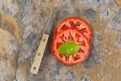 Basil leaf and sliced tomato with knife on real stone board Stock Photos