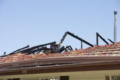 Stock Photo of Fire damaged roof of house with chared timber beams