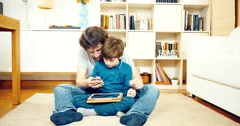 Father and son playing with tablet and cell phone at home Stock Footage