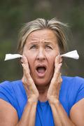 Portrait Stressed woman with earplugs against noise - stock photo