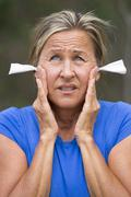 Stressed woman with earplugs noise protection outdoor - stock photo