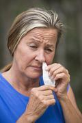 Woman tissue in nose suffering hayfever allergy Stock Photos