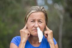 Woman with tissue in running nose and finger in ears Stock Photos