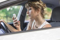 Young woman using mobile phone while driving a car Kuvituskuvat