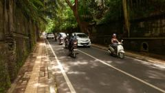 Deep cutting way, Balinese road, Jalan Raya Ubud, motorbike and car traffic Stock Footage