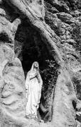 Statue of the Madonna placed in a cavity in the rock. Stock Photos
