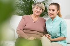 Old female with professional caregiver Stock Photos