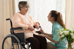 Caregiver helping old female - stock photo