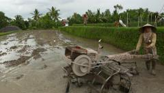 Balinese peasant drive two wheel tractor with rotary tiller on boggy paddy field - stock footage