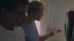 Woman and man looking out plane window Stock Footage