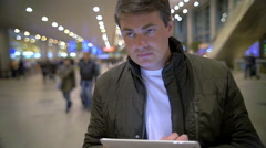 Man with Tablet PC in Airport or Railway Terminal Stock Footage