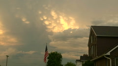 Storm front moving over house with USA flag Stock Footage