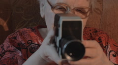 Senior woman filming with retro video camera Stock Footage