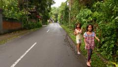 Two little Indonesian girl walk on roadside, towards camera, tropical village Stock Footage