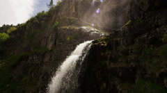 Slow motion waterfall with lush green plants growing on rocky mountainside Stock Footage