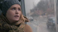 Young sad woman in the bus on a dull rainy day - stock footage