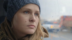 Frustrated and sad woman traveling by bus on rainy day - stock footage