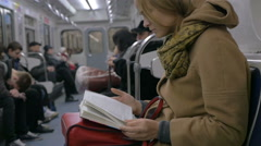 Woman Reading a Book in Tube Train Stock Footage