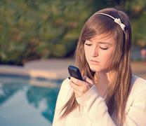 Pretty Teen Girl Looking Unhappily at Cell Phone Stock Photos