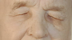 Senior woman opening and closing eyes Stock Footage