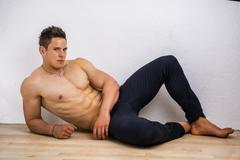 Stock Photo of Handsome young bodybuilder laying down on the floor