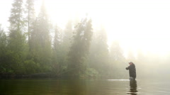 Man Reeling in a Fish from a River Enveloped by Fog - stock footage