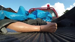 The foot of a manikin in pickup car represents a dead civilian man - stock footage