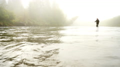Man Fly-Fishing in a River Enveloped by Fog - stock footage