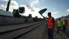 Safety officer signals with a flag to train engineer that the road is safe - stock footage