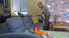 Father man hoover dust from sofa around baby daughter. 4K Stock Footage