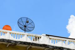 Stock Photo of Satellite dish on the roof with blue sky.