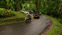Rather busy rural serpentine turn in front of bridge, tropical forest Stock Footage