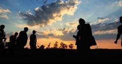 Group of business people silhouettes walking over sunset sky background. 4K UHD - stock footage