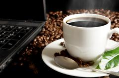 Stock Photo of Cup of black coffee with mist with laptop, green coffee leaf, coffee beans at